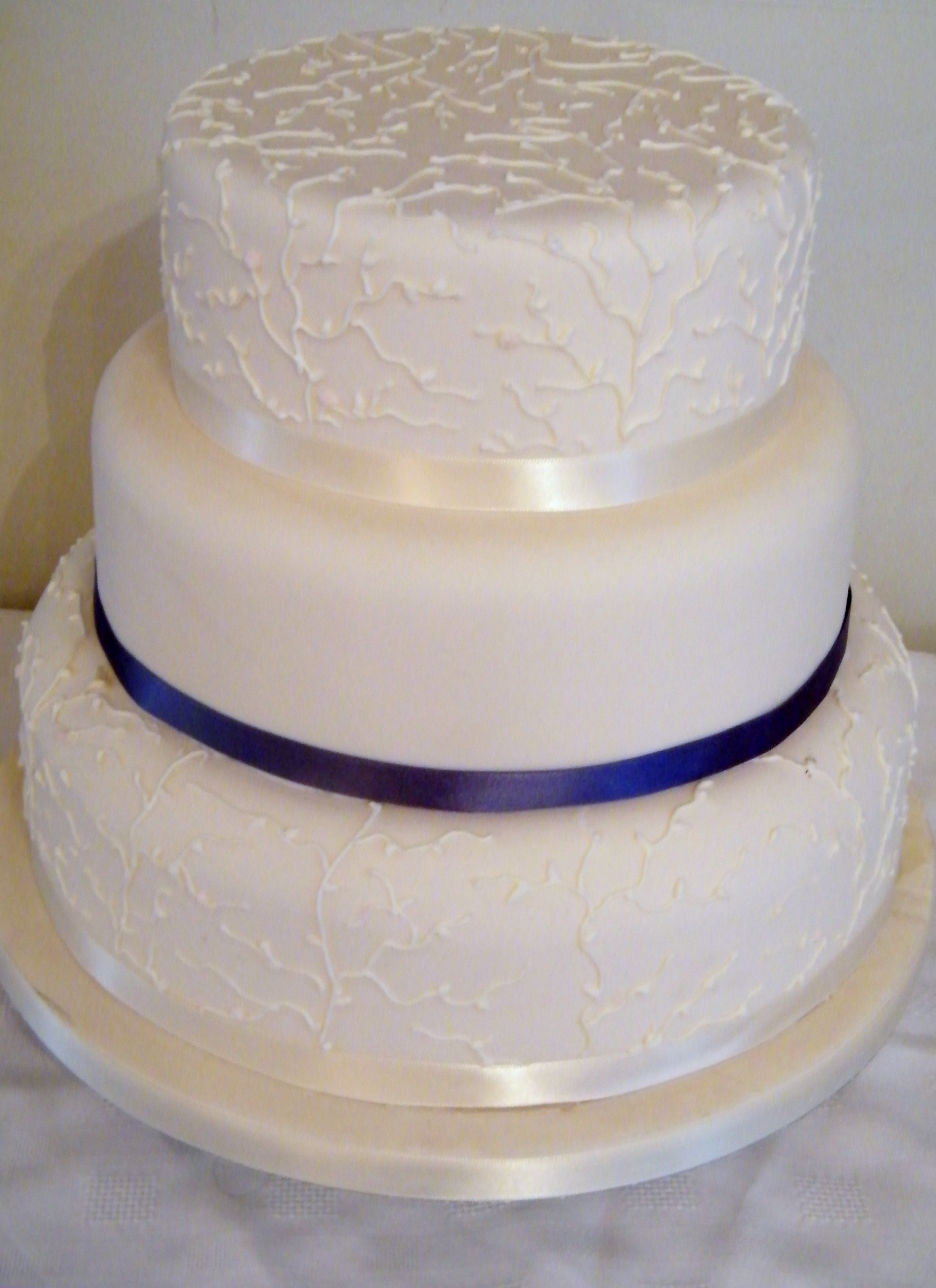 3 tier wedding cake with blue ribbon